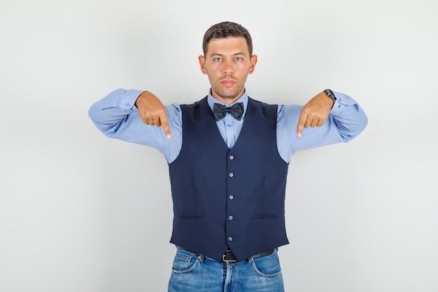 Молодой человек в костюме, джинсы, указывая пальцами вниз и выглядящий серьезным
