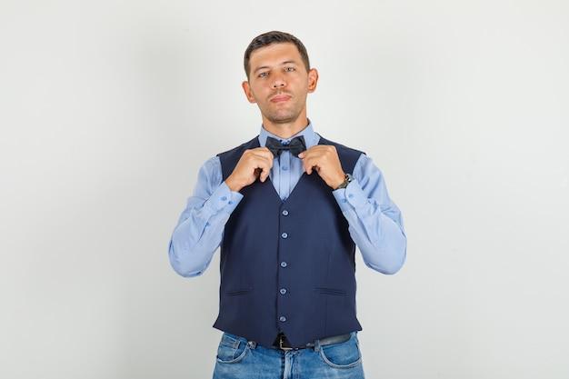 Молодой человек в костюме, джинсы позирует, держа галстук-бабочку