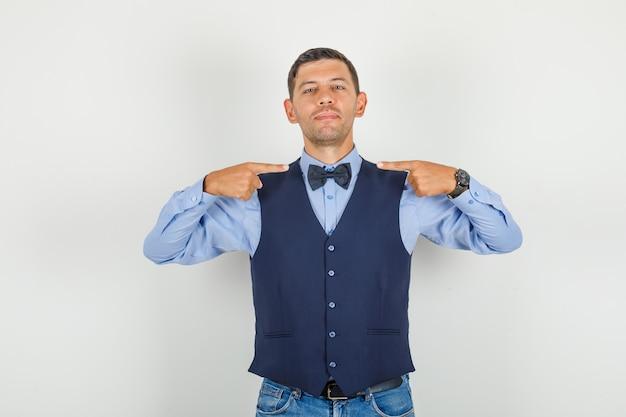 Молодой человек в костюме, джинсах показывает свой галстук-бабочку и выглядит веселым
