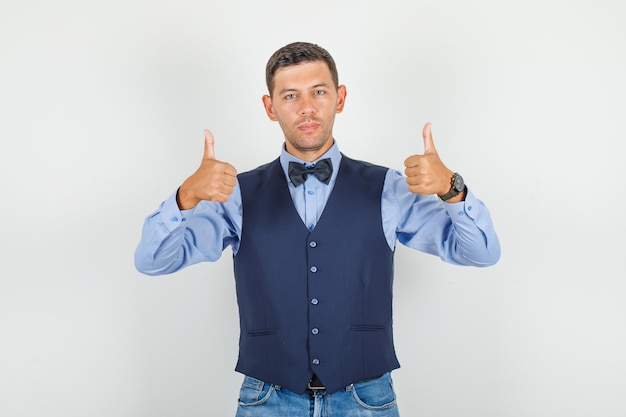 Молодой человек в костюме, джинсах показывает палец вверх и выглядит довольным