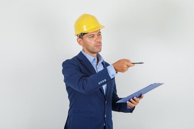 スーツを着た若い男、ペンでさして指している安全ヘルメットと忙しい探して
