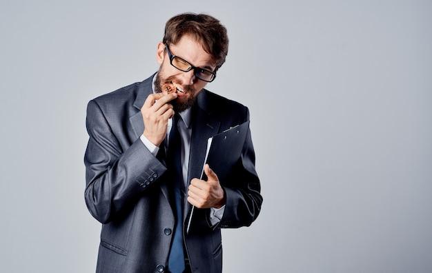 Молодой человек в костюме с документами в руках модели монеты биткойн криптовалюты. фото высокого качества