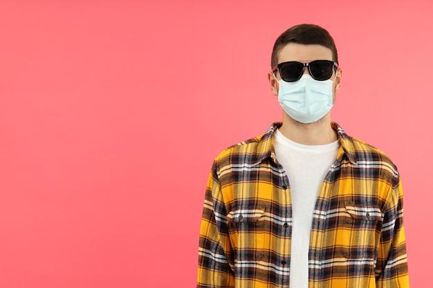 Молодой человек в солнцезащитных очках и маске на розовом фоне, место для текста.