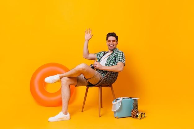 Молодой человек в солнечных очках наслаждается отпуском на фоне надувного круга и чемодана. парень сидит на деревянном стуле, пьет пиво и машет рукой.