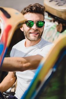 カブリオレのサングラスの若い男