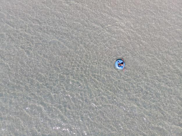 그의 여름 휴가와 바다에서 고무 링에 편안한 수영복에 젊은 남자