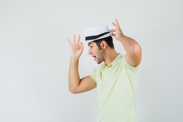 彼の帽子を調整し、エレガントに見えるtシャツの若い男