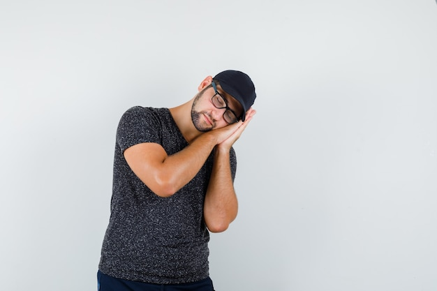 Молодой человек в футболке и кепке, в джинсах опирается на ладони как подушку и выглядит спокойным