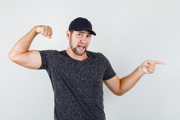 Молодой человек в футболке и кепке поднимает кулак, указывая в сторону и выглядит уверенно