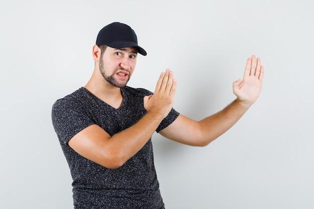 T- 셔츠와 모자 가라테 절단 제스처를 보여주는 젊은 남자와 심각한 찾고