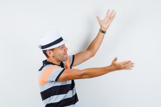 Молодой человек в футболке и шляпе поднимает руки и смотрит печально.