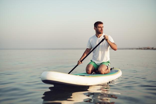 바다에서 sup 보드에 떠 있는 티셔츠와 반바지에 젊은 남자