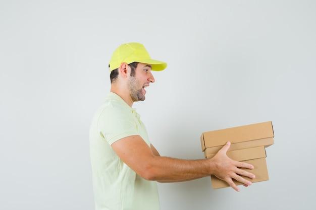 段ボール箱を配達するtシャツの帽子の若い男