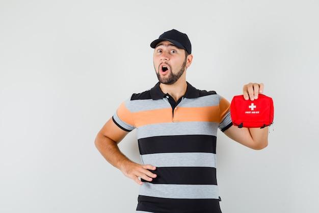 T- 셔츠에 젊은 남자, 응급 처치 키트를 들고 걱정, 전면보기 모자.