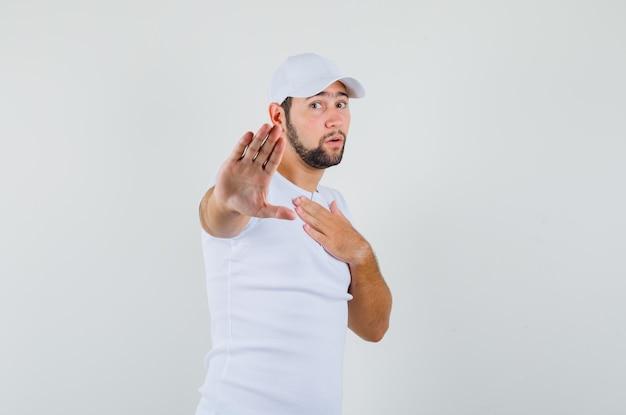 Молодой человек в футболке, кепке, держащей руку на груди, показывая жест остановки и возбужденный, вид спереди.
