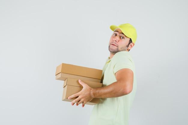重い段ボール箱を保持しているtシャツの帽子の若い男