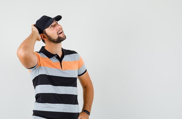 Молодой человек в футболке, кепке, глядя с рукой на голову и мечтательно, вид спереди.