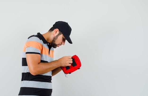 T- 셔츠에있는 젊은이, 응급 처치 키트를 열고 불안해 보이는 모자.
