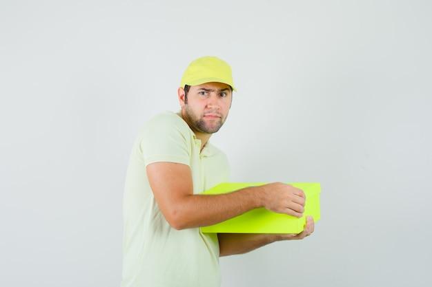 선물 상자를 열고 호기심을 찾고 티셔츠 모자에 젊은 남자
