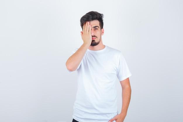 手で目を覆い、自信を持って見えるtシャツの若い男