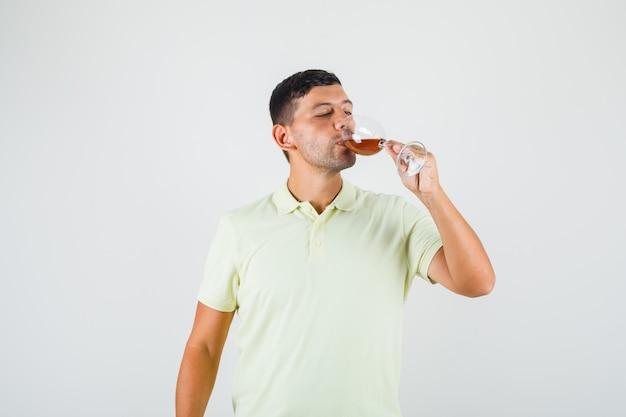 アルコールのガラスを飲むtシャツの若い男。
