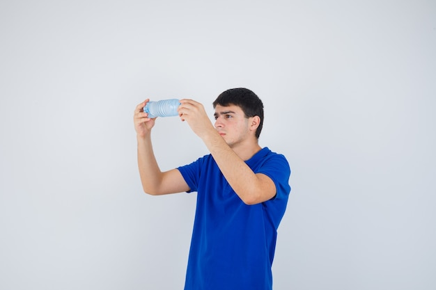 Молодой человек в футболке изучает пластиковую бутылку и смотрит внимательно, вид спереди.
