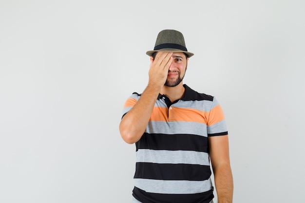 Tシャツ、片方の目に手をつないで、恥ずかしそうに見える帽子、正面図の若い男。