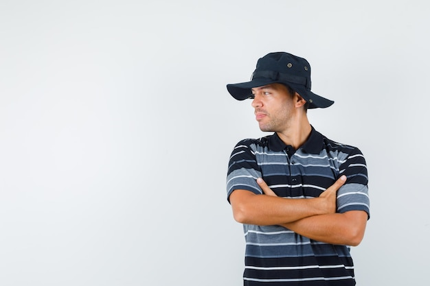 Tシャツを着た若い男、腕を組んで脇を見て、かわいく見える帽子、正面図。