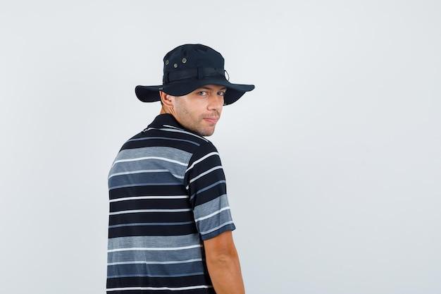 Tシャツを着た若い男、肩越しに見て、陽気に見える帽子、背面図。