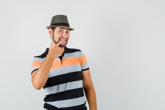 Молодой человек в футболке, шляпе, указывая на зубы и красивый, вид спереди.