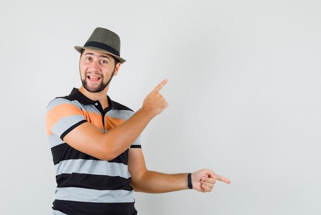 Tシャツを着た若い男、指を上下に向け、優柔不断に見える帽子、正面図。