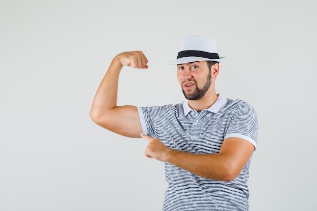 Молодой человек в футболке, шляпе показывает мышцы руки и выглядит бесстрашным, вид спереди.