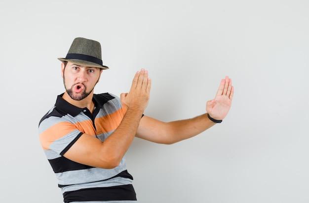 T- 셔츠에 젊은 남자, 가라테 절단 제스처를 보여주는 모자와 자신감, 전면보기를 찾고.