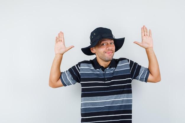 Tシャツを着た若い男、降伏のジェスチャーで手のひらを示し、陽気に見える帽子、正面図。