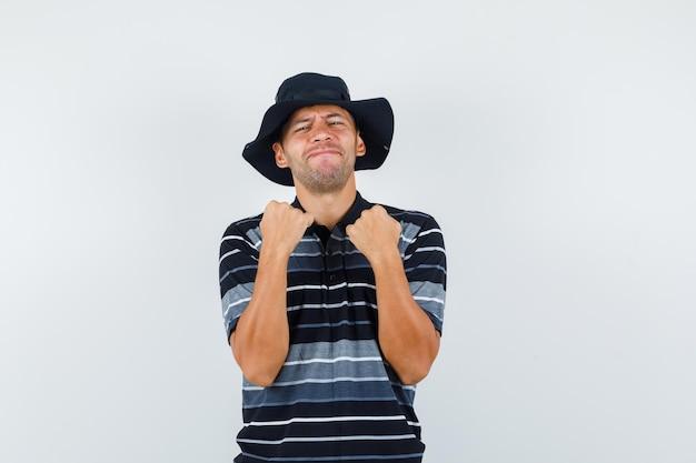 Молодой человек в футболке, шляпе показывает жест победителя и выглядит удачливым, вид спереди.