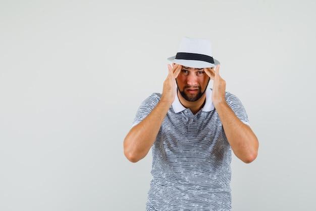 T- 셔츠에 젊은 남자, 두통으로 고통 받고 피곤, 전면보기 모자.