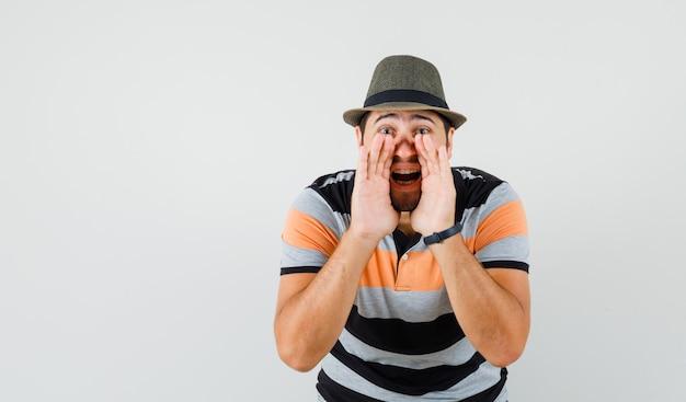 Tシャツを着た若い男、口の近くの手で秘密を告げる帽子、正面図。