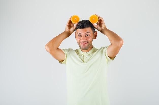 Молодой человек в футболке держит дольки апельсина на голове и выглядит забавно