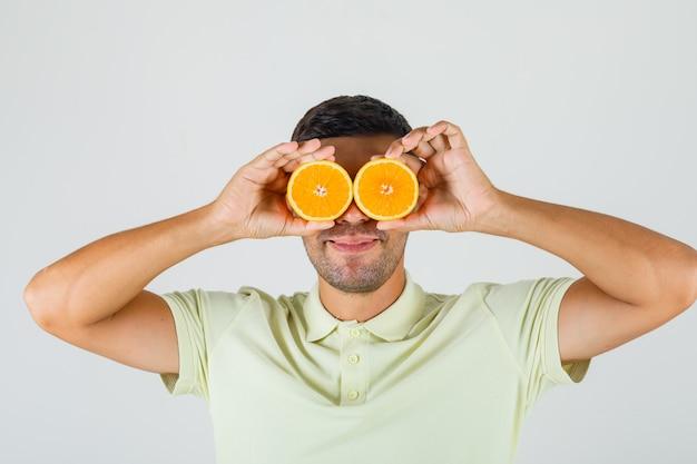 Молодой человек в футболке держит дольки апельсина над глазами