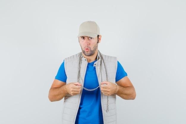 彼のチェーンネックレスを保持し、驚いて見える、正面図、tシャツ、ジャケット、キャップの若い男。