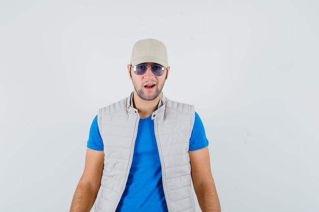 T- 셔츠, 재킷, 모자 카메라를보고 자신감, 전면보기에서 젊은 남자.