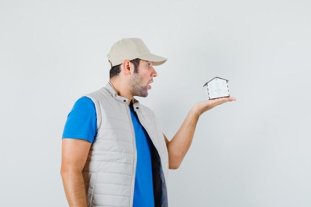 Tシャツ、ジャケット、キャップの若い男が家のモデルを見て驚いて、正面図を見てください。