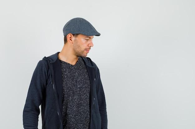 Tシャツ、ジャケット、キャップを見下ろし、物思いにふける、正面図の若い男。