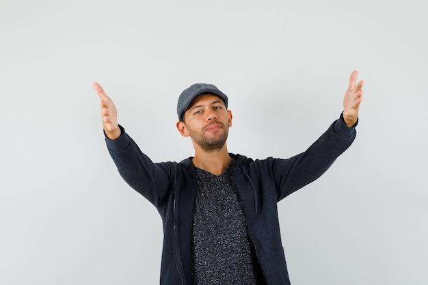 Молодой человек в футболке, куртке, кепке открывает руки для объятий и выглядит добрым, вид спереди.