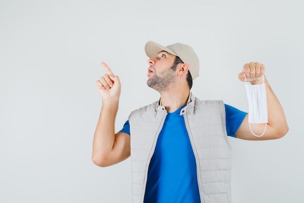 Tシャツ、ジャケット、キャップを上向き、医療マスクを保持し、驚いて見える、正面図の若い男。