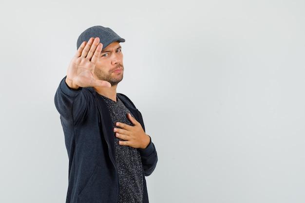 Молодой человек в футболке, пиджаке, кепке показывает жест отказа, взявшись за руку на груди, вид спереди.