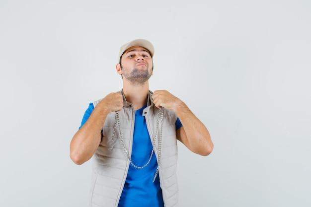 Tシャツ、ジャケット、キャップを身に着けているチェーンネックレスと自信を持って見える、正面図の若い男。