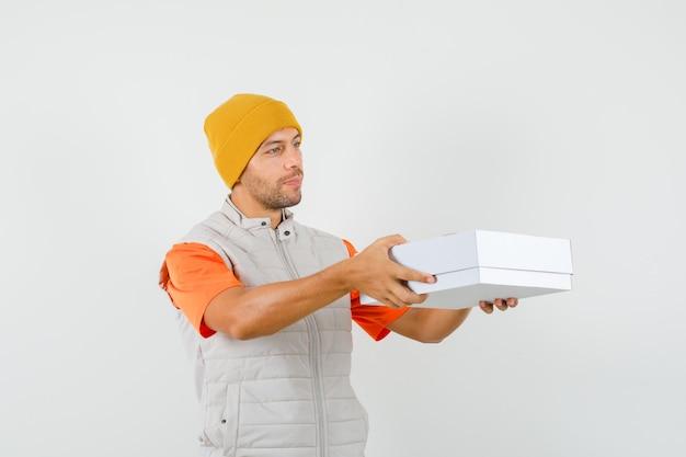 Tシャツ、ジャケット、帽子の段ボール箱を提供し、穏やかに見える、正面図の若い男。
