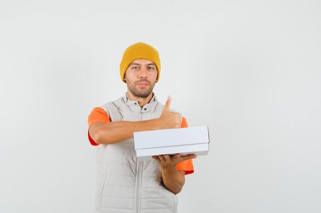 Tシャツ、ジャケット、段ボール箱を保持している帽子の若い男