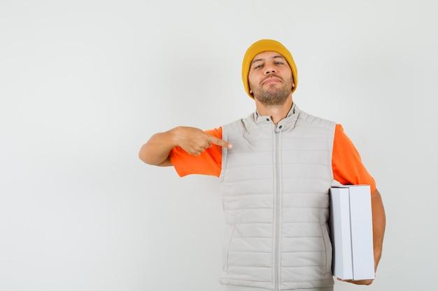 Tシャツ、ジャケット、帽子の段ボール箱を指して、誇らしげに見える若い男